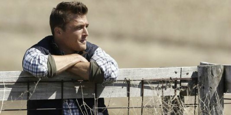 Chris Soules is leaning on a fence.