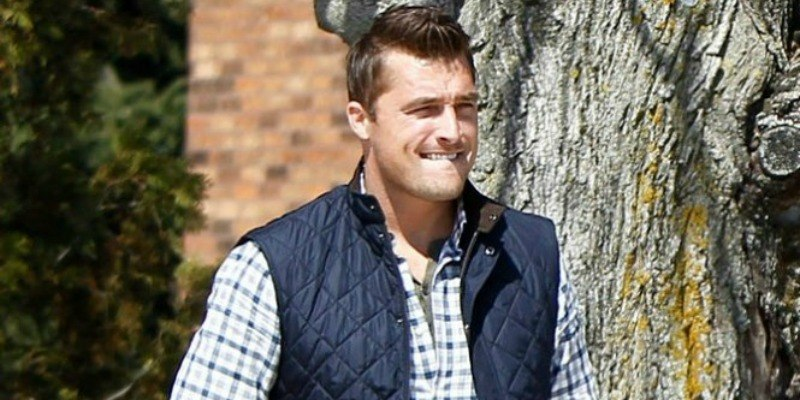 Chris Soules is biting his lip while walking near some trees.