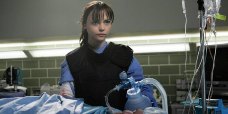 Christina Ricci is wearing a vest while operating on a patient.