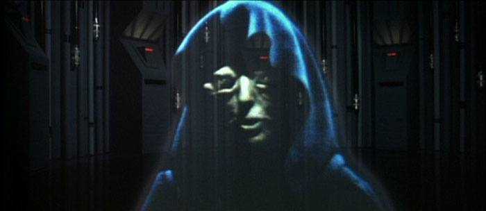 A hologram of Emperor Palpatine, shrouded in shadow and wearing a black hood