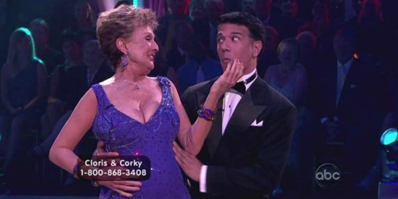 Cloris Leachman is holding Corky Ballas face as he looks at her.
