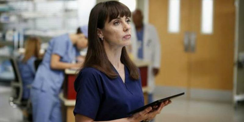 Constance Zimmer is in blue scrubs and is holding a tablet.