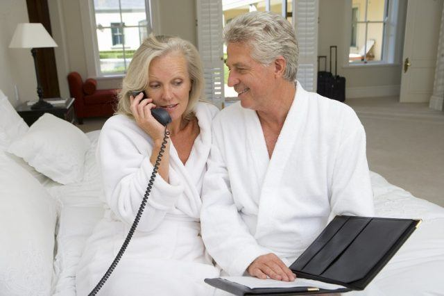Mature couple sitting on bed with the woman talking on the phone
