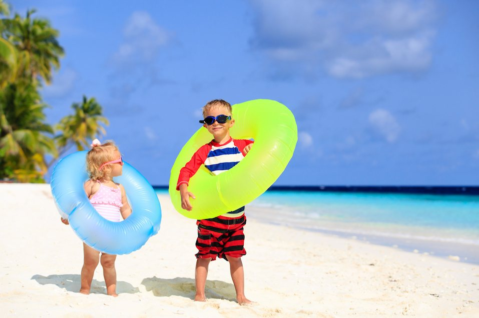 little boy and toddler girl play on tropical beach
