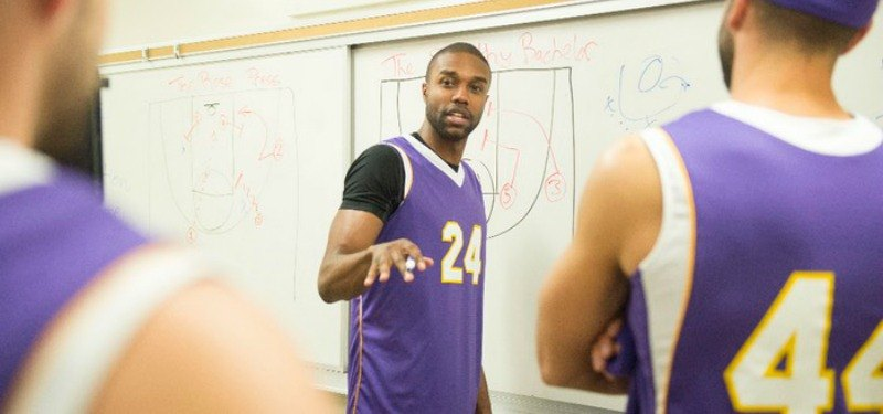 DeMario is talking to his basketball team mates while in front of a chalk board.