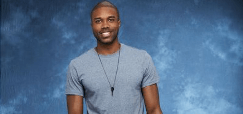 DeMario is wearing a grey shirt and is standing in front of a blue background.