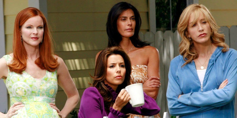 The cast of Desperate Housewives is standing together on someone's front lawn.
