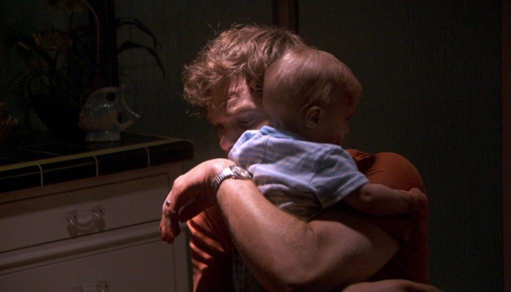 Michael C. Hall as Dexter Morgan holding his son Harrison covered in blood