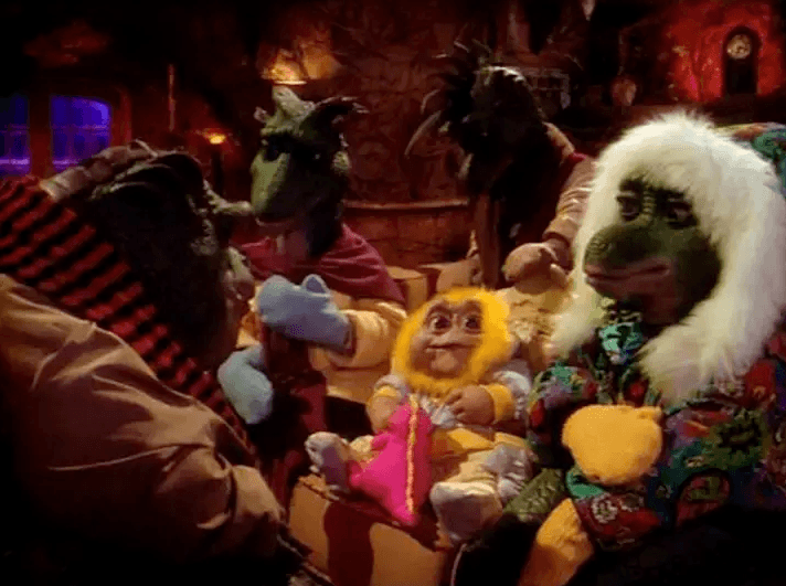 Muppet dinosaurs bundled up in winter clothes inside