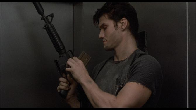 Dolph Lundgren, loading a large gun and wearing a grey tshirt