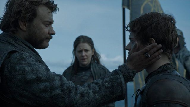 Euron holds Theons head in his hands, as the two look intensely at each other on a cliff above a beach.