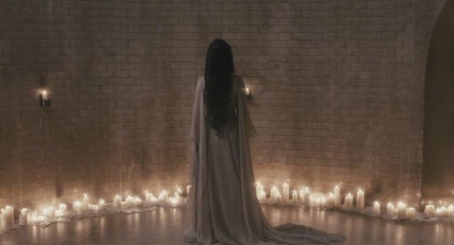 Eva Green in a white robe facing away in front of a brick wall and many candles