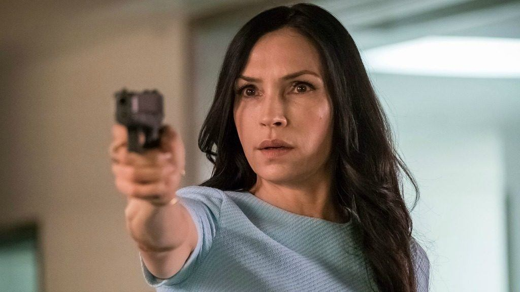 Famke Janssen as Susan Scott 'Scottie' Hargrave wearing a light blue shirt and pointing a gun off screen on The Blacklist: Redemption