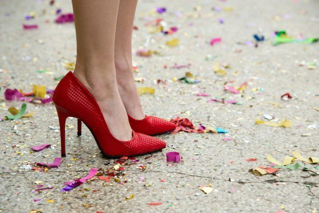 female legs in red shoes against confetti and garlands