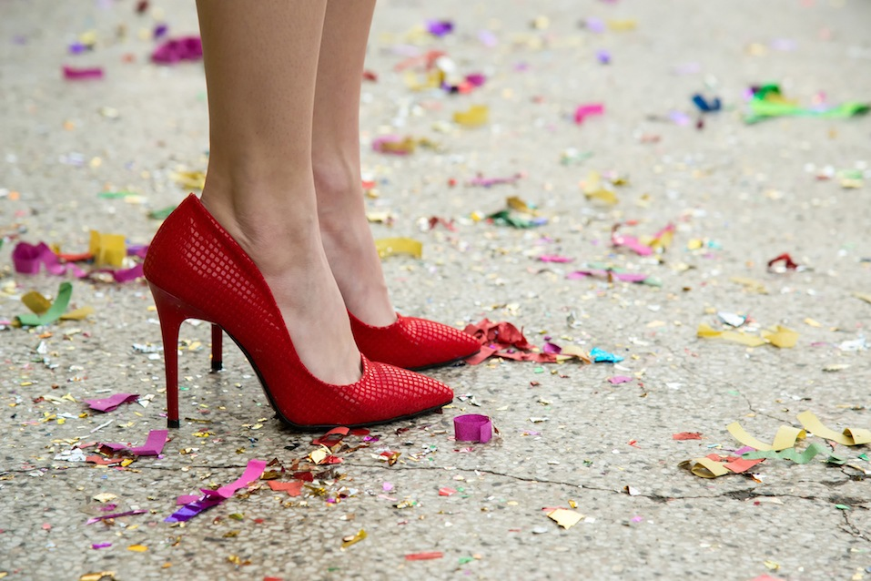 female legs in red shoes against the confetti and garlands - selective focus, copy space