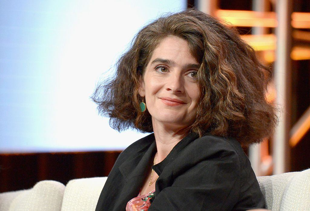 Gaby Hoffmann smiles while sitting on a white couch