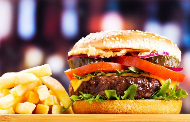 Hamburger with fries on wooden table.