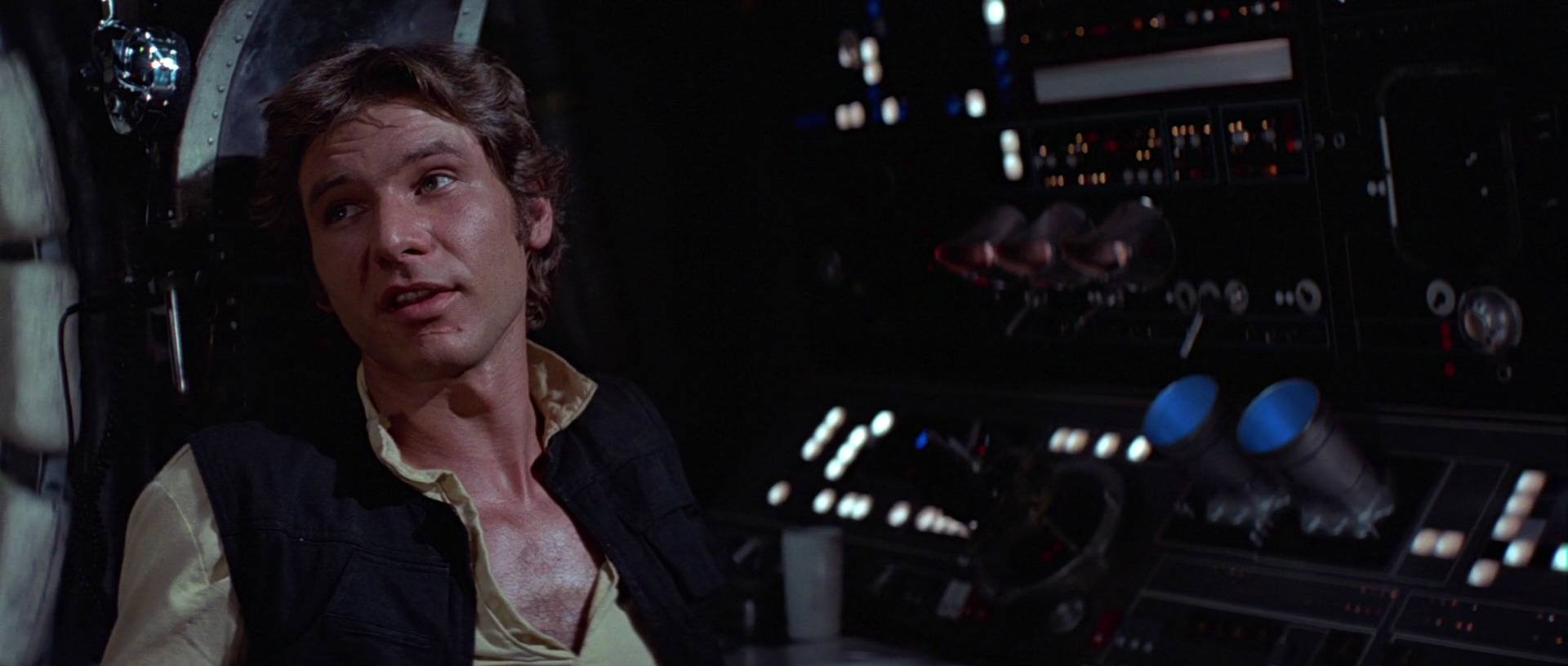 Han Solo sitting in a chair with his feet up, looking to the left of the frame and speaking