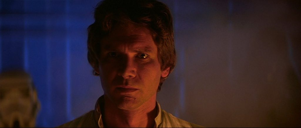 Han Solo in a darkly lit chamber, looking grimly on
