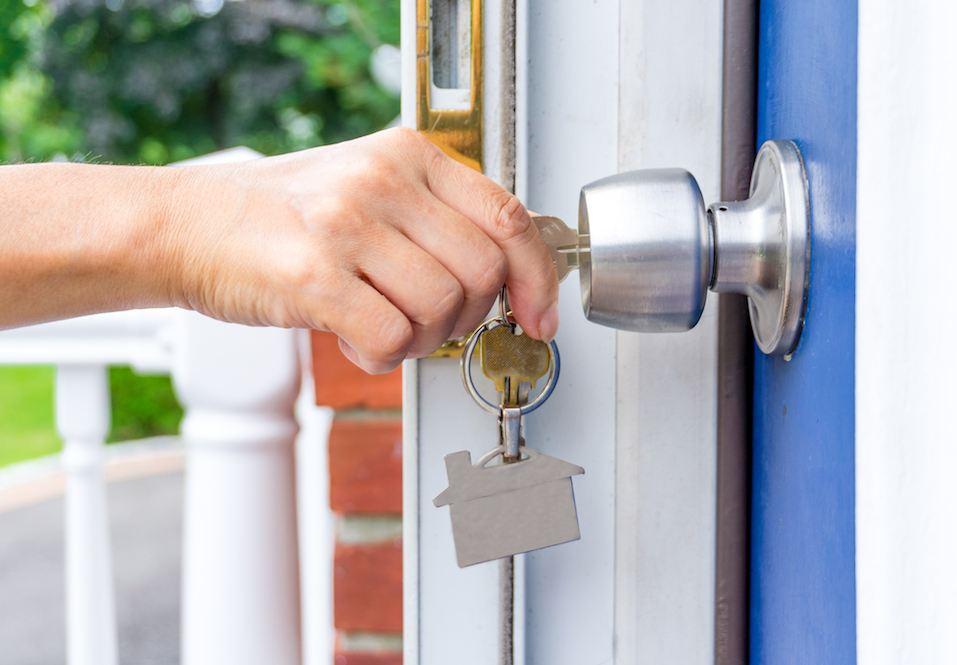 hand opening a door with keys