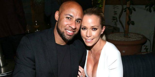 Hank Baskett and Kendra Wilkinson pose together smiling at the paparazzi.