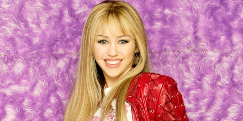 Hannah Montana has blonde hair and is wearing a red leather jacket.