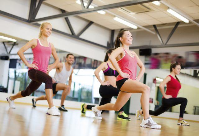 A group of people doing lunges during a class at a studio