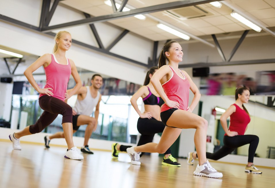 happy people doing lunge exercises in the gym