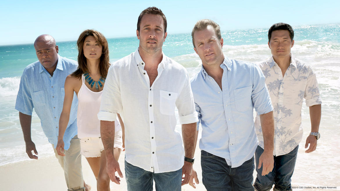 The cast of Hawaii Five-O walks on a beach with the ocean in the background