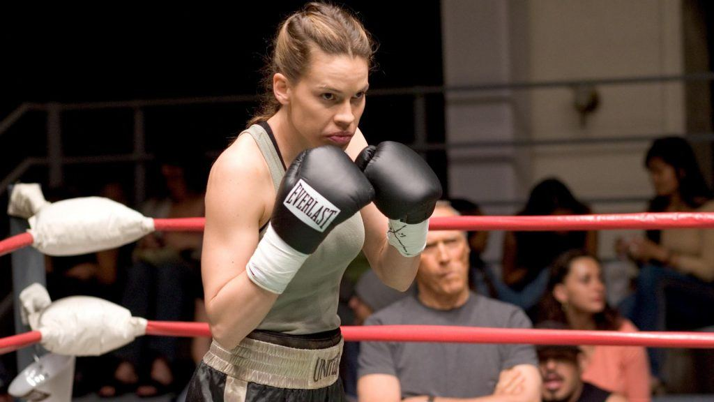 Hilary Swank with her arms up while boxing