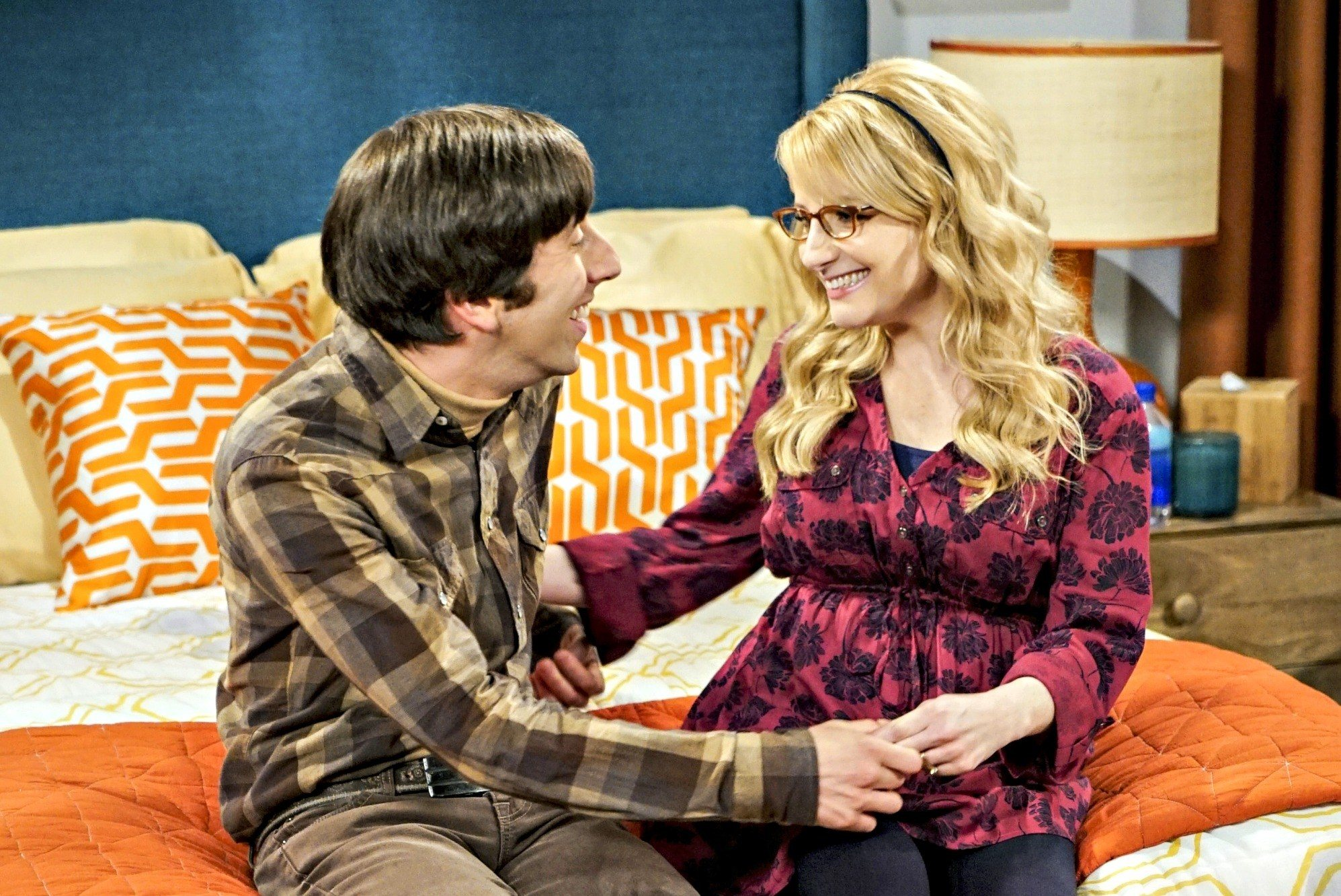 Howard and Bernadette hold hands while sitting on a bed in The Big Bang Theory