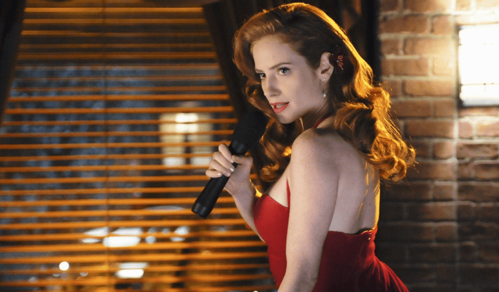 Jaime Ray Newman in a red dress singing into a microphone