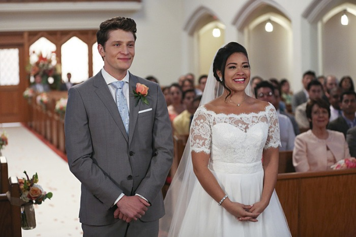 Michael and Jane are crying happy tears standing next to one another in a church at their wedding