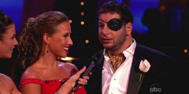 Jeffrey Ross is wearing an eye patch and is talking into a microphone as Edyta Sliwinska looks at him smiling.