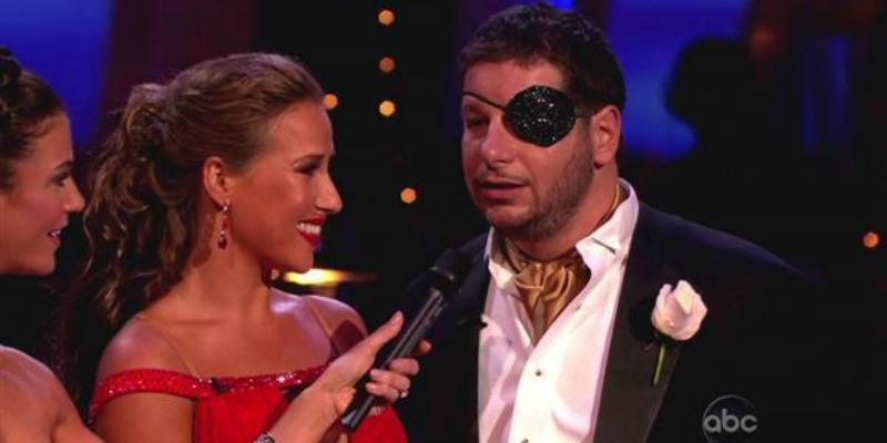 Jeffrey Ross is wearing an eye patch and is talking into a microphone as Edyta Sliwinskaare looks at him smiling.