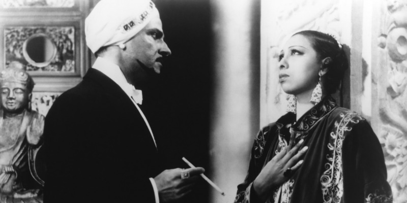 Josphine Baker has her hand over her chest as a man looks at her holding a cigarette.