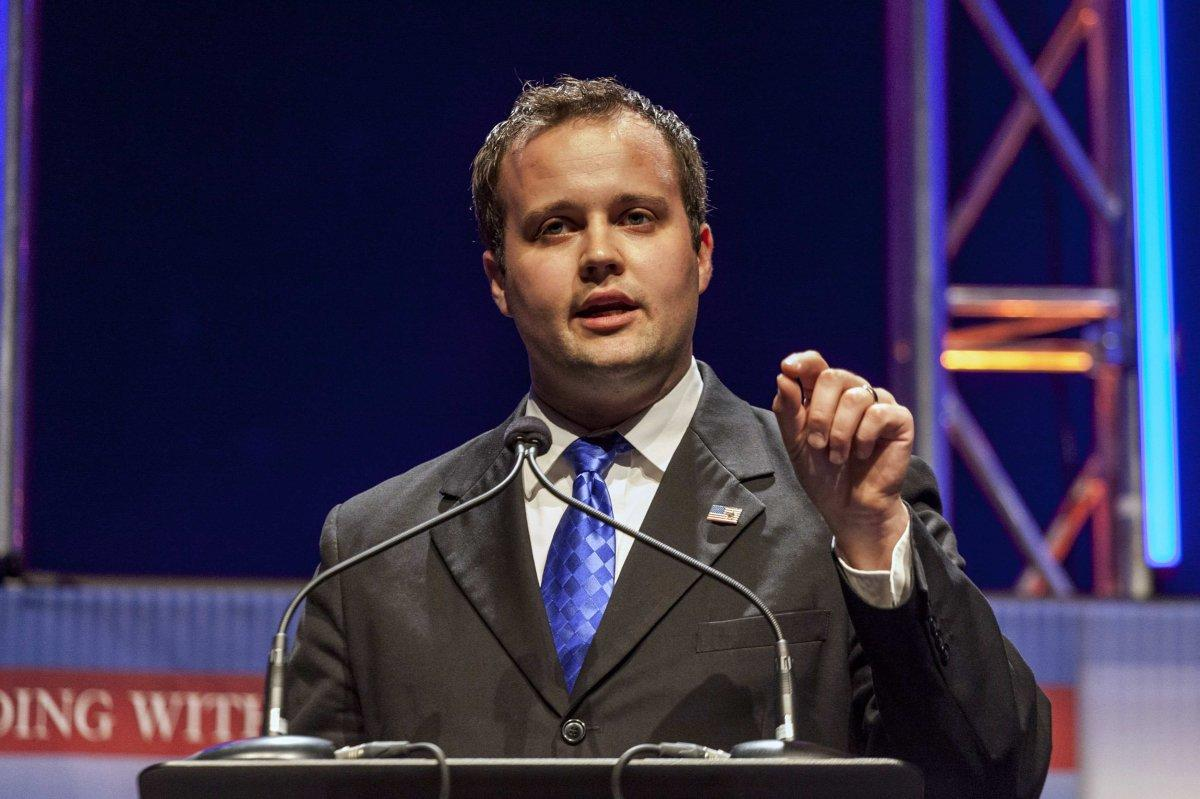 Josh Duggar wearing a suit, and speaking into a microphone while pointing