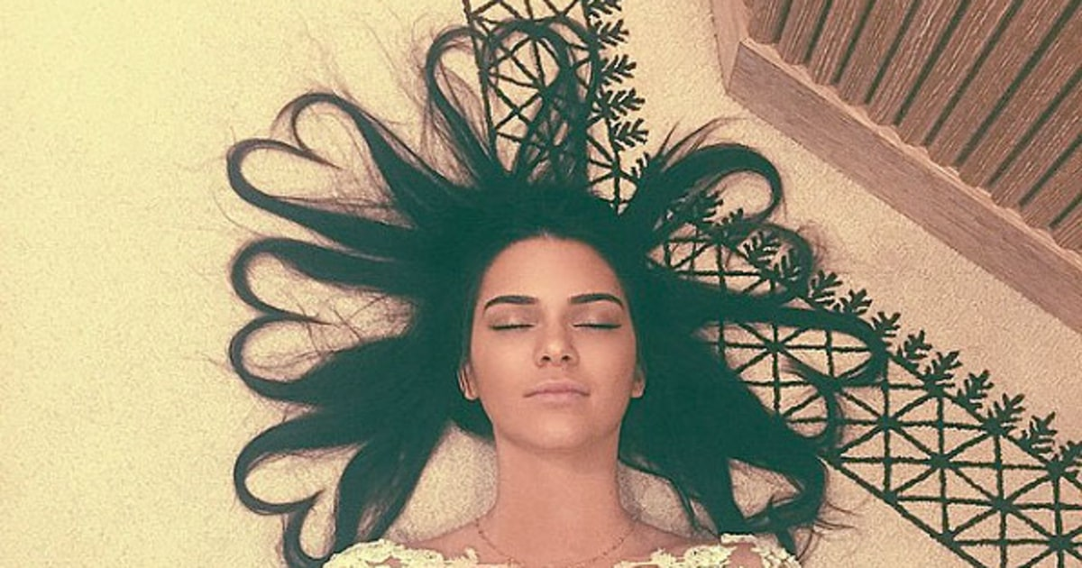 Kendall Jenner lays on the floor with her hair arranged in hearts around her head