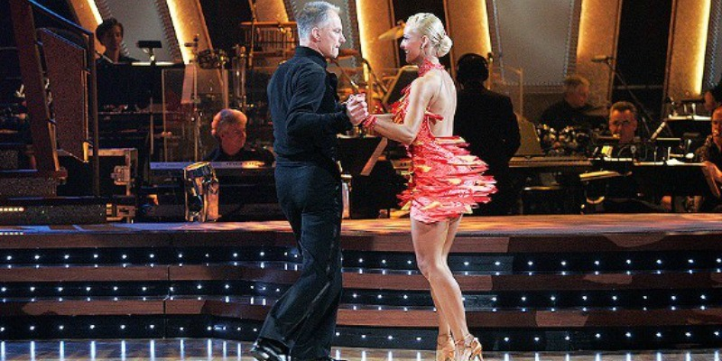 Kenny Mayne and Andrea Hale are twisting together as they dance.