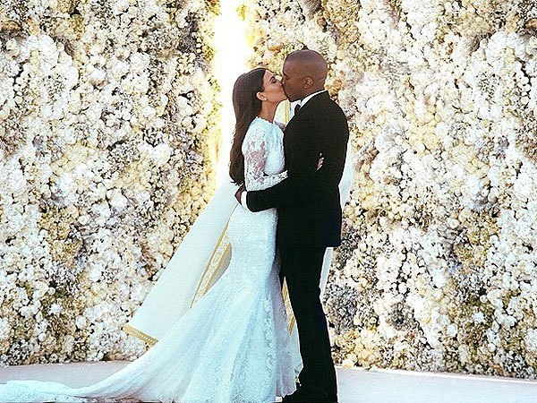 Kim Kardashian and Kanye West kiss in front of a wall of flowers at their wedding