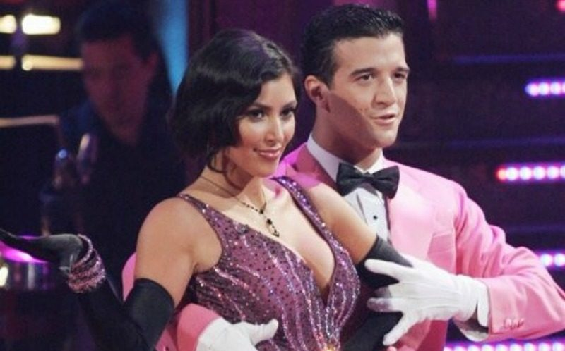 Kim Kardashian and Mark Ballas pose together in purple and pink outfits as they dance.