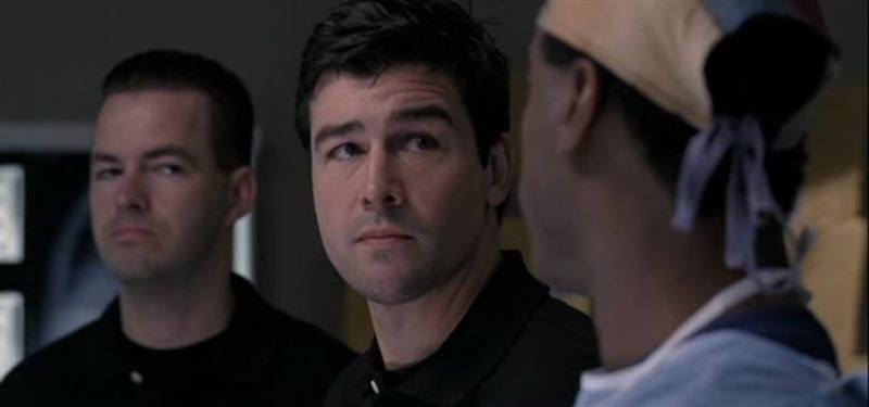 Kyle Chandler is dressed as a cop and is looking at a surgeon.