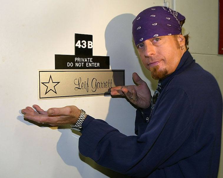 Leif Garrett in a purple bandana gestures to a star name plaque on his dressing room.