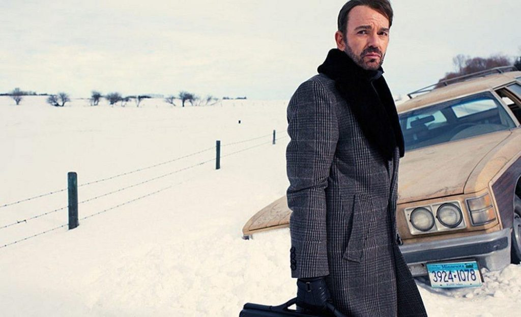 Billy Bob Thornton as Lorne Malvo, wearing a long grey trenchoat in the snow, holding a suitcase in his right hand