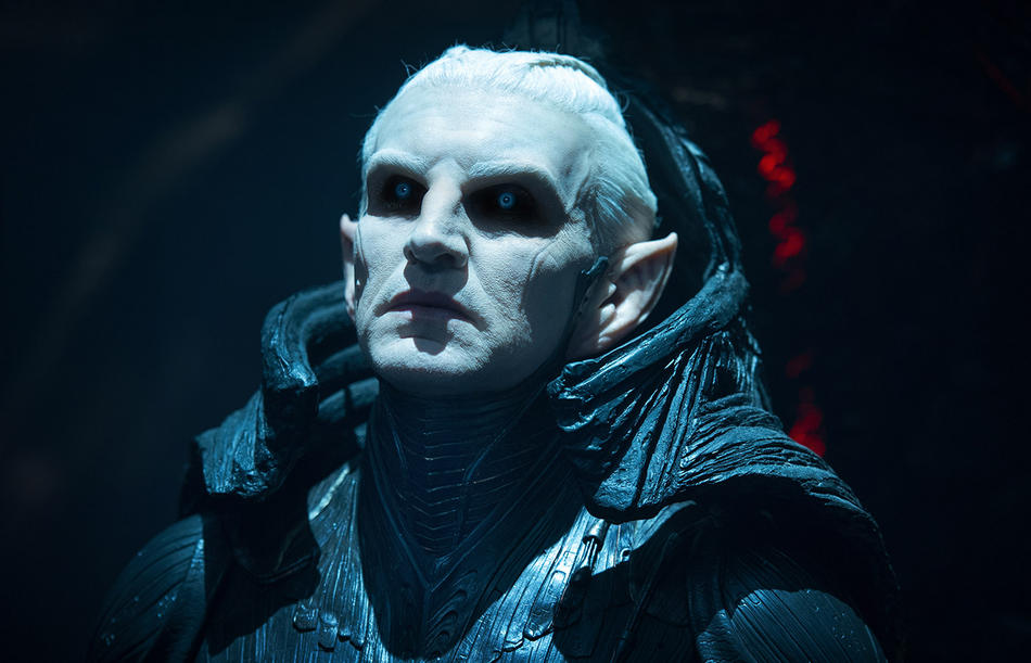 Malekith, wearing armor that extends up around his neck, looking menacingly off to the right of the frame