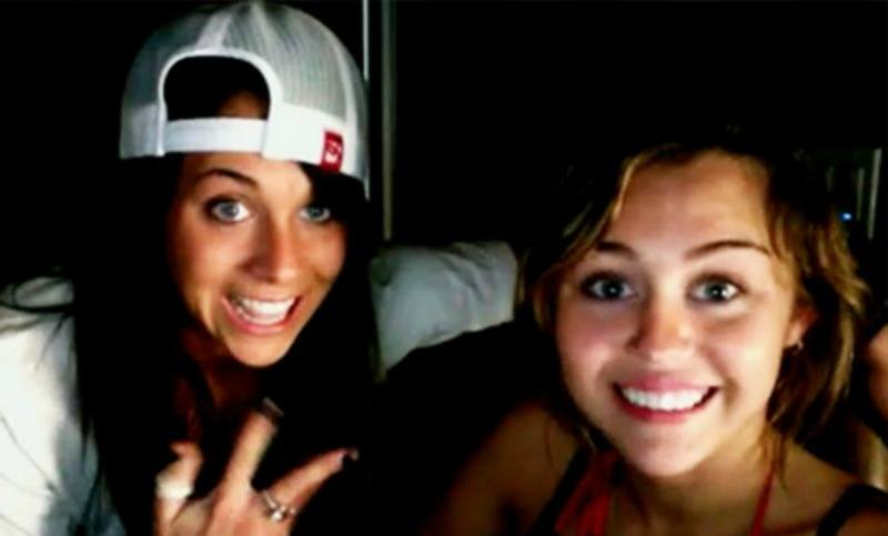 Mandy Jiroux is wearing a backwards cap and is posing next to a smiling Miley Cyrus.