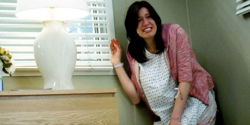Mandy Moore is crying in a hospital gown and is in a corner of the room.