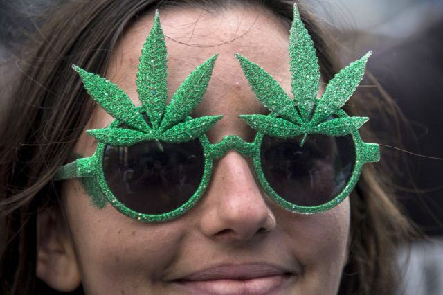 A woman wears green glasses with decorative marijuana leaves.