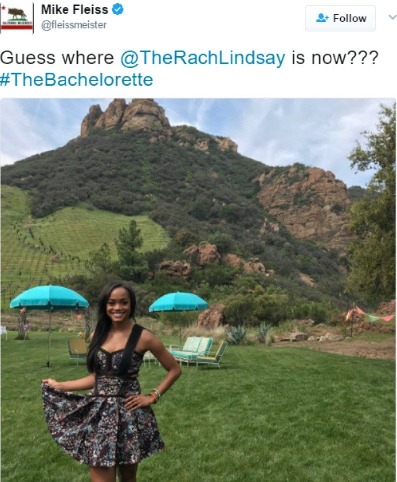 Rachel Lindsay poses in a dress in front of a beautiful green hill.