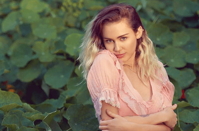 Miley Cyrus poses in some greenery in a pink dress